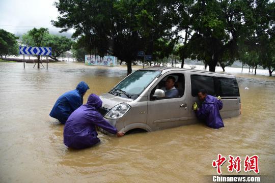 7月2日,一辆车辆在柳州市滨江路被泡,市民忙着推车。 王以照 摄