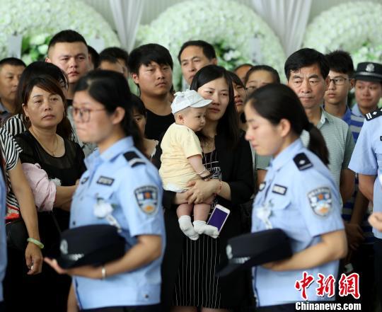 牺牲民警钱宗清的妻子和6个月大的女儿来送钱宗清最后一程。 沈果 摄