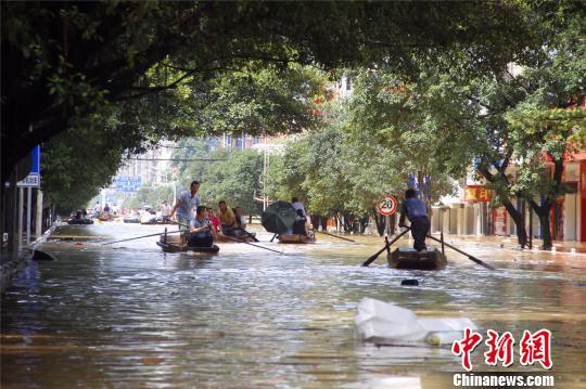 广西融水县城遭洪水浸泡 民警消防划船转移产妇