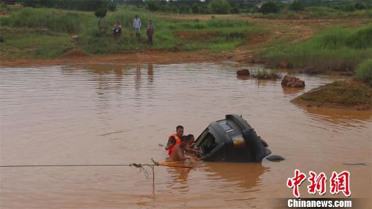 救济职员打捞落水车辆。 钟欣 摄