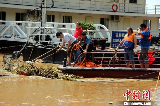 图为志愿者清理江中杂物。 卢文伟 摄