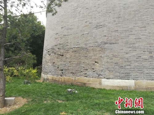 """宛平城墙上的坑孔。有一位老人说,这就是当年""""七七事变""""日军炮击宛平城留下的弹孔。上官云 摄"""