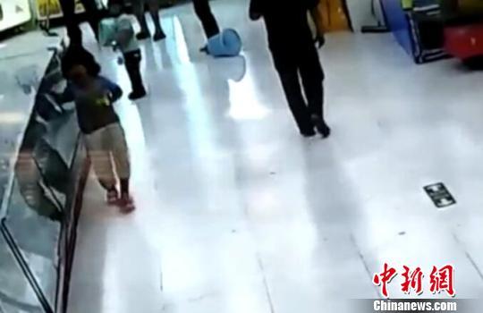 被市民拉开后,女童扶着柜台一瘸一倒的离去。(视频截图)