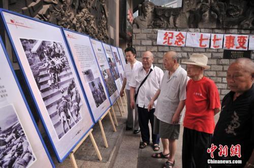 """资料图:2014年7月7日,重庆大轰炸经历者和遇难者家属在大轰炸遗址前举行""""七七事变""""全民族抗战爆发77周年纪念活动。 陈超 摄"""