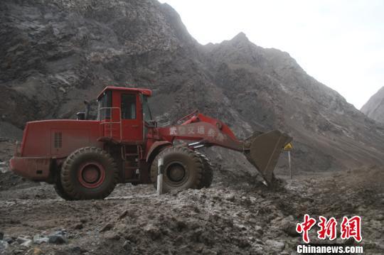 驾驶挖掘机清理路面淤泥。 王劼 摄