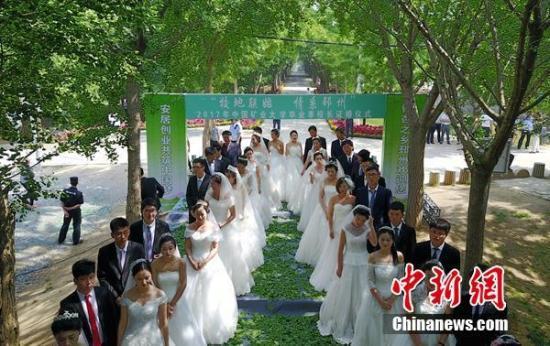 """中国矿大20对学生情侣在毕业离校之前,在银杏""""时光隧道""""举行集体婚礼。韦超 摄"""