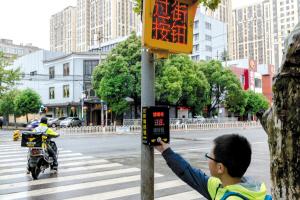 一名小朋友使用学府路上的手动信号灯。都市时报 赵黎浩 图
