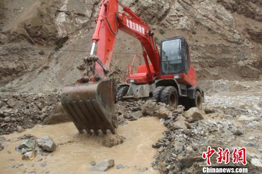 图为官兵驾驶挖掘机全力抢通。 王劼 摄