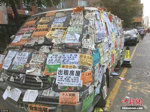 资料图:一辆大马路边的废旧汽车上被贴满了各式各样的房屋租售小广告。图片来源:视觉中国