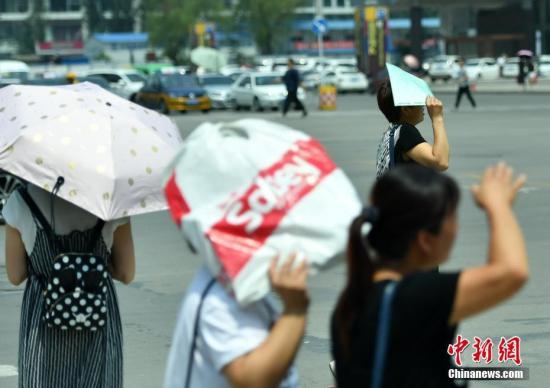 7月11日,河北石家庄民众高温中出行。该省气象台发布高温红色预警信号,受强暖气团影响,预计当日下午,部分地区最高气温可达37-39℃,局地超过40℃。 中新社记者 翟羽佳 摄