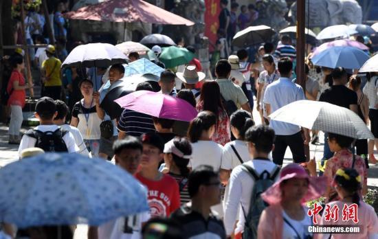 厦门一景点游客们纷纷打伞遮挡烈日。张斌 摄