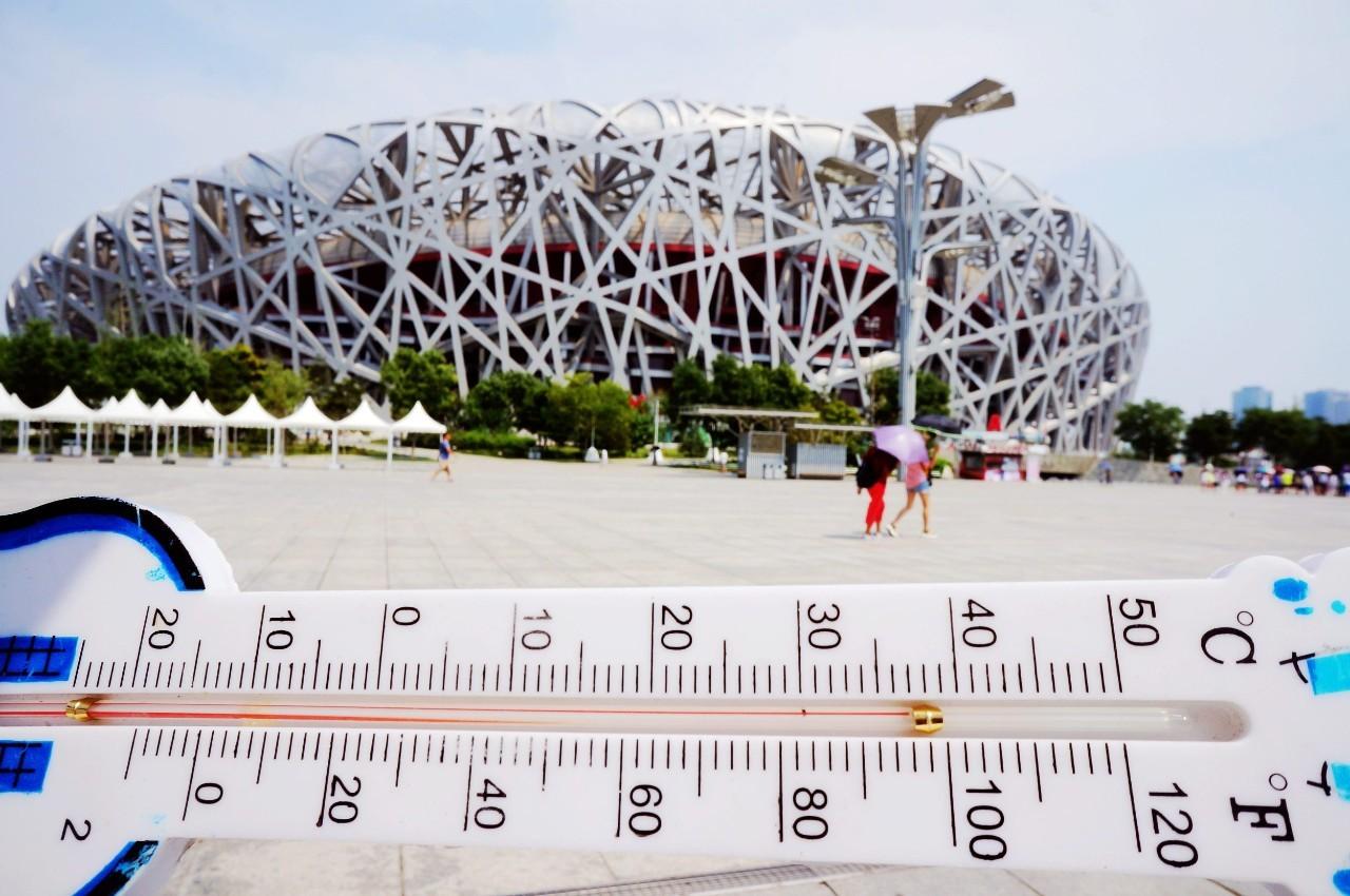△7月12日,北京一位市民在奥体公园鸟巢前用温度计丈量其时的气温,温度计刻度显示高达40度左右。