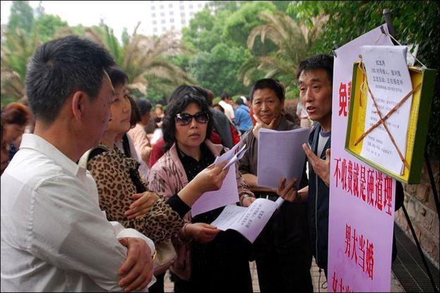 """上海人民广场某""""相亲角""""父母忙着给孩子找对象(图片来源:BBC)"""