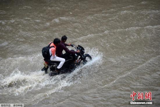 资料图:印度进入雨季,民众骑摩托车经过被大水淹没的街道。