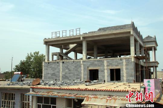 在建楼房顶部南侧的装饰性花墙倒塌,只剩下几条孤零零的钢筋架。被砸邻居房顶,有大量青灰色砖块杂乱堆积。 于俊亮 摄