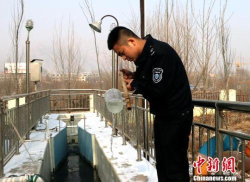 资料图:西宁市环境监察支队执法人员对相关设施进行检查。 孙睿 摄
