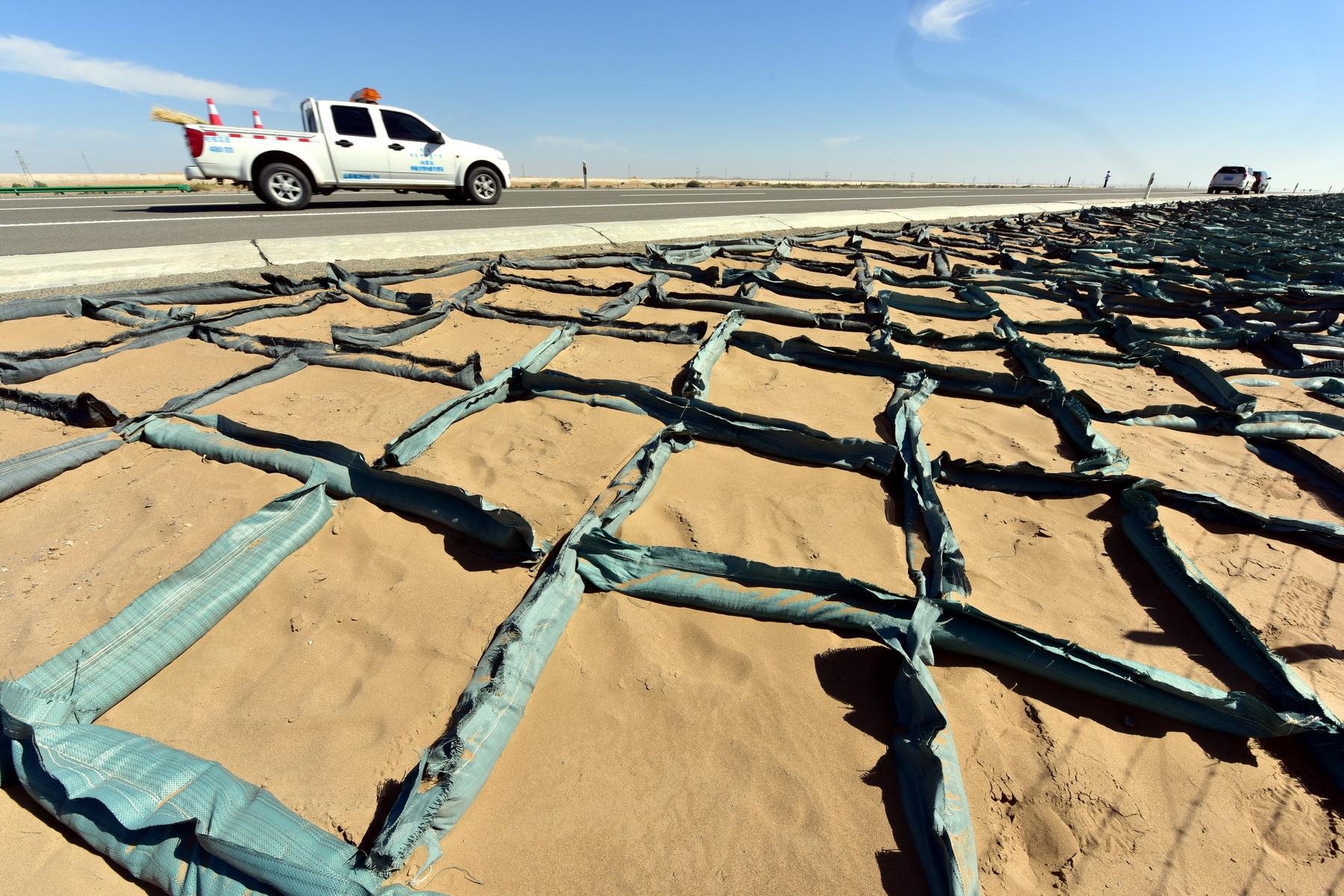 京新高速公路内蒙古临河至白疙瘩段沿途设置的固沙障.摄影/章轲