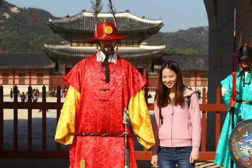 材料图片:在韩国首尔景福宫外,中国旅客与韩国守城门将合影。新华社记者 姚琪琳 摄