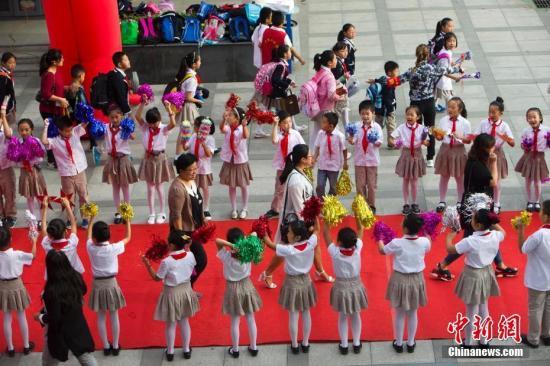 资料图:2016年9月9日,山西太原新建路小学的教师们在学生们的欢呼簇拥下走红毯展风采、秀签名,并接受他们崇高的敬礼与祝福。张云 摄