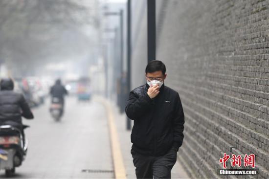 资料图:雾霾天气市民戴口罩出行。张远 摄