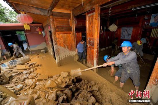 湖北省五峰土家族自治县7月14日至15日遭遇特大暴雨袭击,导致山洪暴发、河水猛涨,基础设施、水利设施损失严重。图为摄救援队帮助受灾户清除家中淤泥。雷勇 摄
