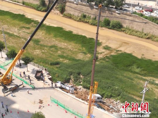 图为延安一河堤垮塌八辆车掉入河槽。 高庆国 摄