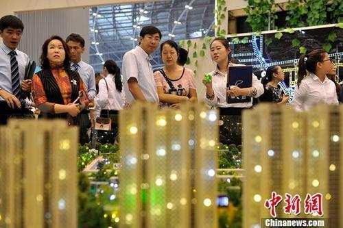 7月18日,山西太原,置业顾问为民众推荐商品房户型。 中新社记者 韦亮 摄