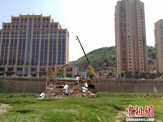 图为陕西延安一河堤垮塌八辆车掉入河槽。 高庆国 摄