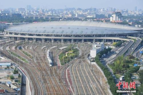 """6月26日,由上海虹桥站始发的G124次""""再起号""""高铁列车准时抵达北京南站。中新社记者 崔楠 摄"""