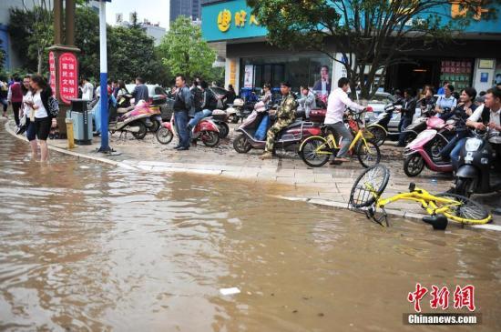 昆明暴雨城市内涝,众多上班族被积水困在路上无法前行。 中新社记者 刘冉阳 摄