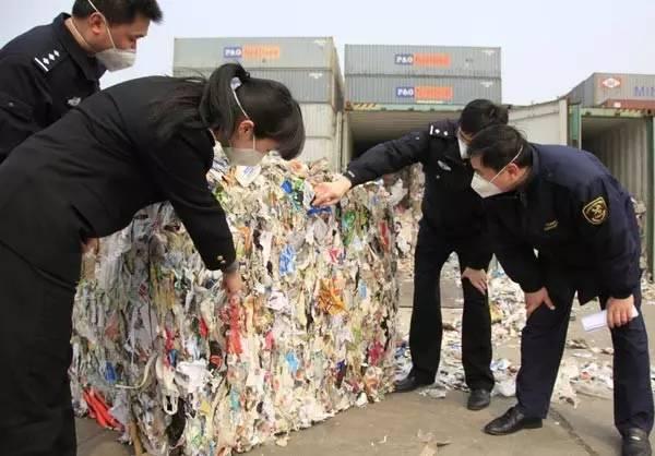 张家港海关职员正在检验走私垃圾(图自中国日报)