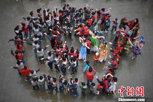 资料图:留守儿童与志愿者一起舞蹈。陈超 摄