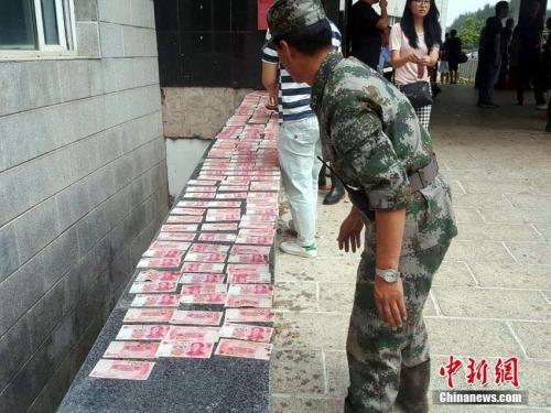资料图:吉林永吉洪灾后清淤现3万现金,救灾官兵全上交。苍雁 摄