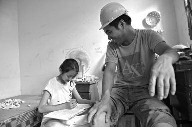 11岁张雅馨在小案板上写作业,一旁的张军才怜爱地看着女儿
