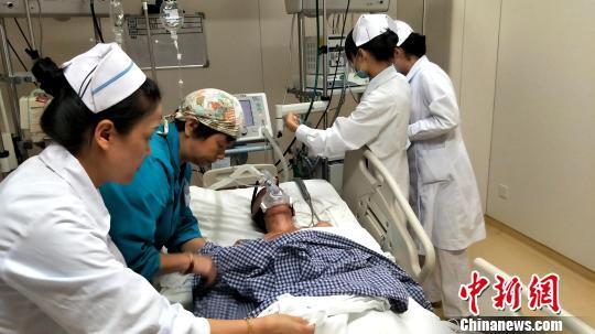 材料图:医护职员为患者插上医疗仪器。 徐志雄 摄