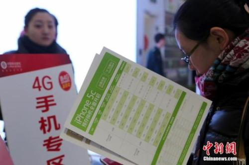 资料图:北京金融街移动营业厅内,顾客正在体验4G手机。中新社发 李慧思 摄
