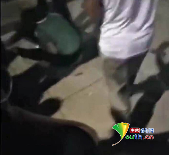 绿衣女子被打的蹲在地上。中国青年网 图