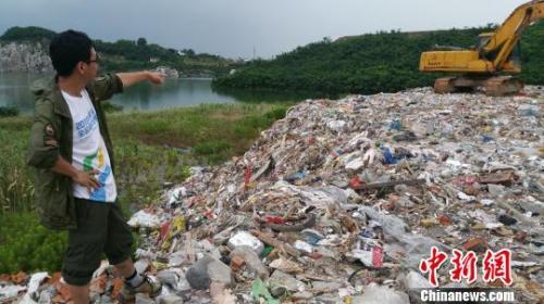 渣滓被倾倒在湖水边(材料图)。 王津 摄