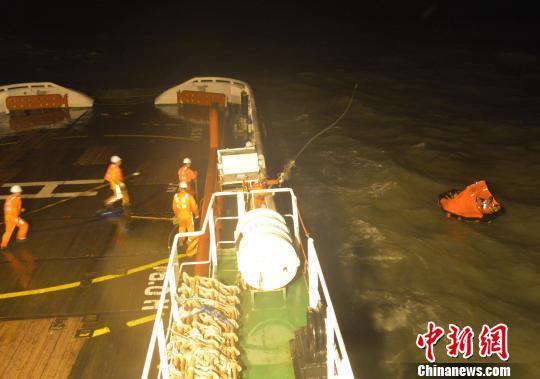 """""""东海救111""""轮上的救济职员向脱险海员抛投救生索。 黄智明 摄"""