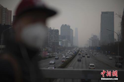 资料图:3月20日,北京市民在雾霾中出行。中新社记者 刘关关 摄