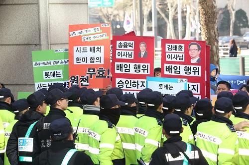 """资料图:韩国民众在位于首尔的乐天集团总部前举行抗议示威活动,并高举反对乐天出让""""萨德""""用地的标语。新华社发"""