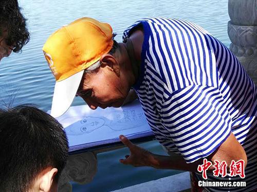 """""""张老太""""在给一个孩子画肖像。中新网记者 宋宇晟 摄"""