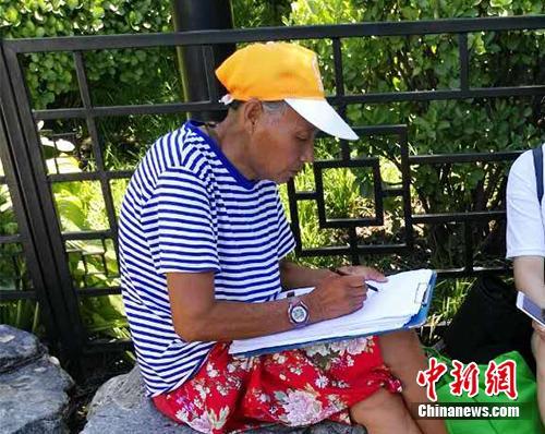 """自称""""张老太""""的画师在什刹海附近画肖像。中新网记者 宋宇晟 摄"""