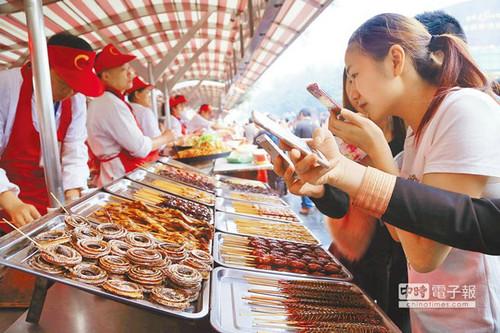 """北京一""""虫子宴""""摊位,摆满串蛇、蜈蚣、蚂蚱、蜘蛛等,不少门客拿出手机拍┞氛。(台湾中时电子报)"""