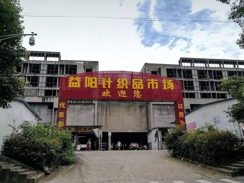 """(2017年7月11日,湖南益阳,烂尾的""""五角大楼""""一侧建起一排临时商铺。图/《财经》记者 鲁伟)"""