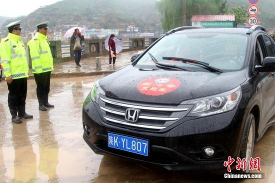 资料图:近日,陕西绥德县境内普降大到暴雨,局部地区出现特大暴雨。全县各镇遭遇了不同程度的洪涝灾害。图为一些爱心车辆在街头送物资。 王永平 摄
