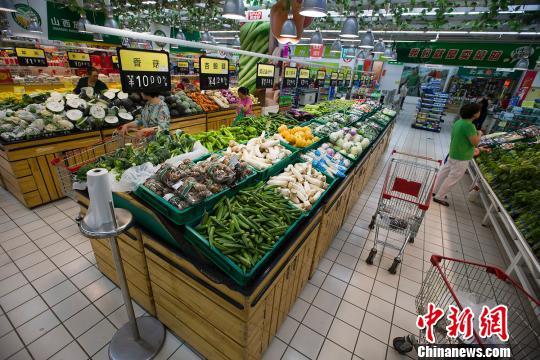 材料图:大众在超市选购蔬菜。 张云 摄