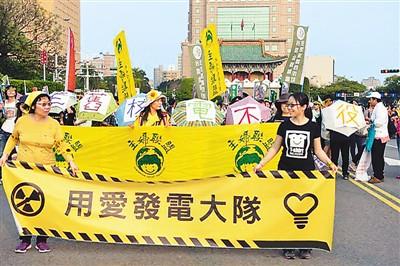 """图为二○一四年的""""反核""""游行中,台湾一些反核人士打出""""用爱发电""""标语。(资料图片)"""