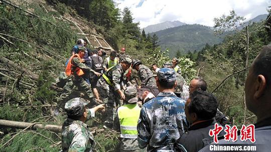 图为救济职员抬着伤者经由飞石路段。 广元救济队供给