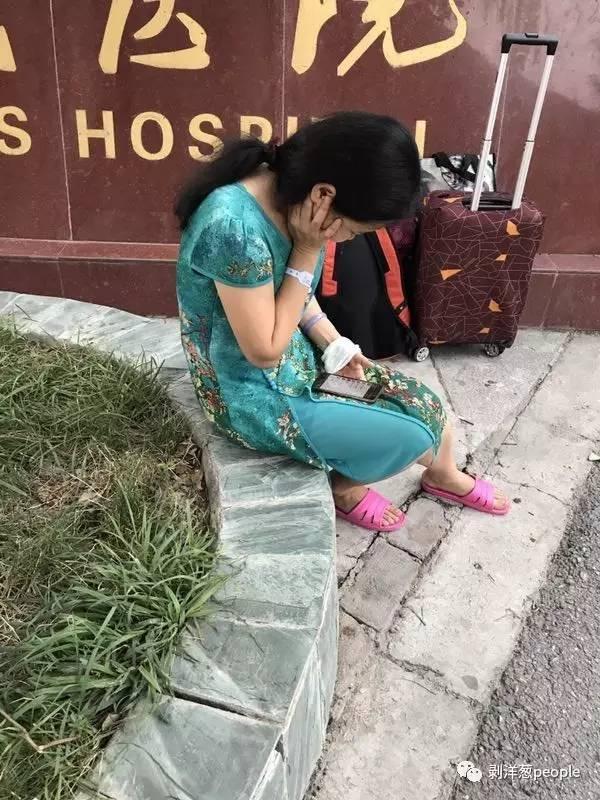 游客赵丽坐在九寨县人民医院门口等待回家的车。新京报记者刘珍妮 摄